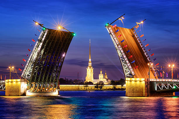 The Palace Bridge on Neva river, St Petersburg, Russia View through the opened bascule Palace Bridge and Neva river to Peter and Paul Fortress at white night time, St Petersburg, Russia bascule bridge stock pictures, royalty-free photos & images