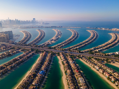 The Palm Jumeirah shaped island in Dubai United Arab Emirates aerial view at sunrise. Famous man made palm shaped island with luxury waterfront villas and hotels surrounded by seaside