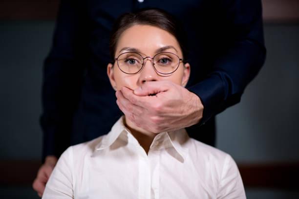 la palma de un hombre cierra la boca de la mujer - foto de stock