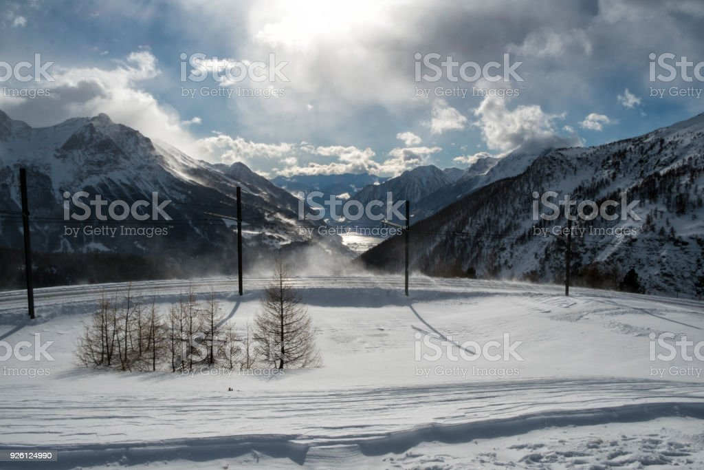 ALP GRUM, SWITZERLAND - January, 2018. The panorama of Lake Poschiavo and the railroad tracks of the Bernina Express train, in winter with snow stock photo