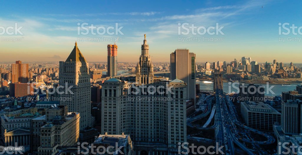The panoramic scenic view to the Manhattan Downtown, over the Brooklyn Bridge and East River toward Brooklyn. The skyline includes the major buildings: Manhattan Municipal Building,  Thurgood Marshall United Square Courthouse, One Brooklyn Bridge Plaza, a stock photo