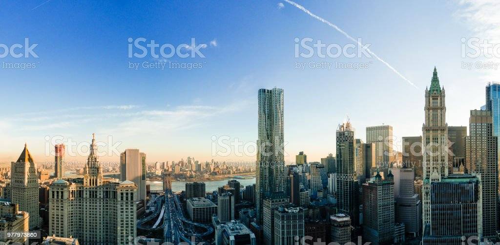 The panoramic scenic view to the Manhattan Downtown, over the Brooklyn Bridge and East River toward Brooklyn. The skyline includes the major buildings: Manhattan Municipal Building, New York by Gehry, Thurgood Marshall United Square Courthouse, Woolworth stock photo
