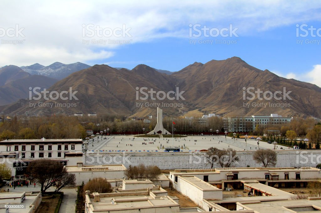 The panoramic view of Lhasa city, in front of  Potala Palace and Palace square, with modern building and mountains, far away a Tibet Peaceful Liberation Monument and blue sky stock photo