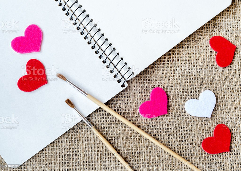 The paper hearts and notebook with brushes on the sackcloth royalty-free stock photo
