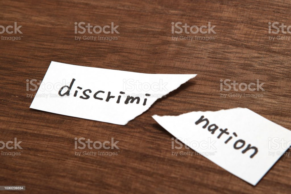 The paper written as discrimination is torn on wood. Concept of abolition of discrimination. stock photo