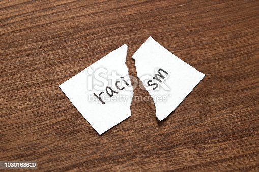 istock The paper written as racism is torn on wood. Concept of abolition of racial discrimination. 1030163620