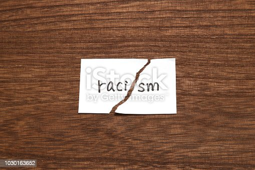 istock The paper written as racism is torn on wood. Concept of abolition of racial discrimination. 1030163652
