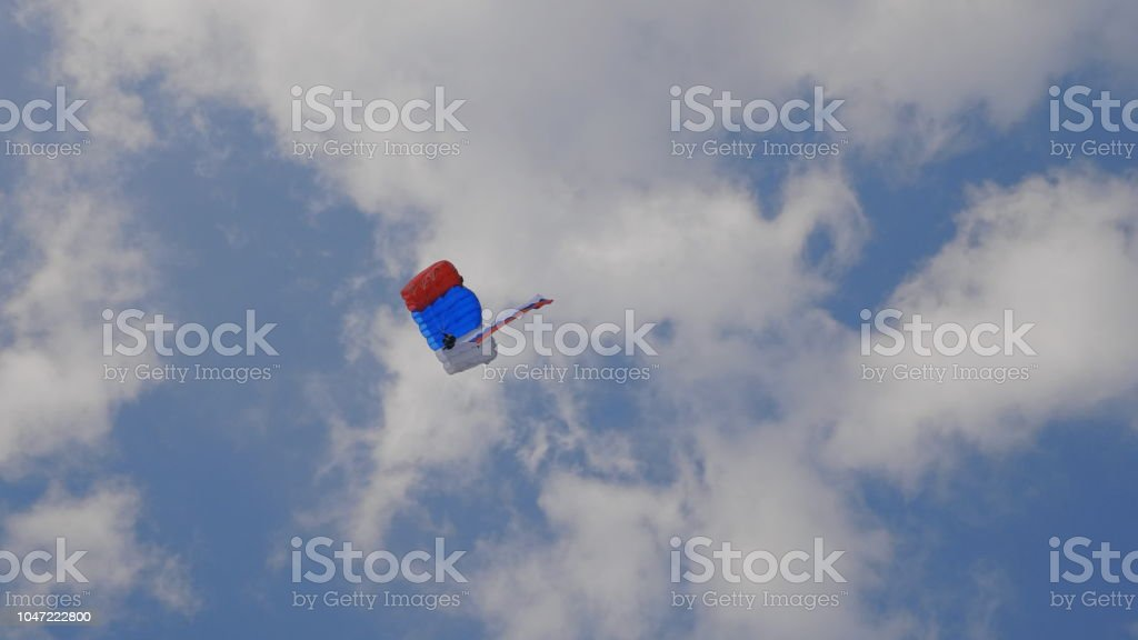 MOSCOW - SEP 2: the paratrooper descends on a parachute with the flag of Russia at a celebration in honor of the 70th anniversary of the launch of the first aircraft An-2 on September 2, 2017 in Moscow, Russia stock photo