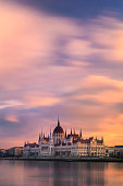 View of the Parliament on the Danube river with romantic clouds during sunrise