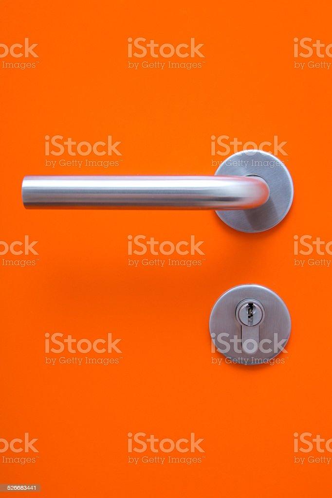the part of orange door with metal handle stock photo