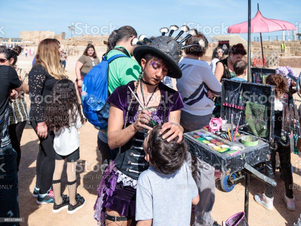 The participant of the Purim festival dressed in fabulous costume, puts a drawing on the boy's face in Caesarea, Israel stock photo