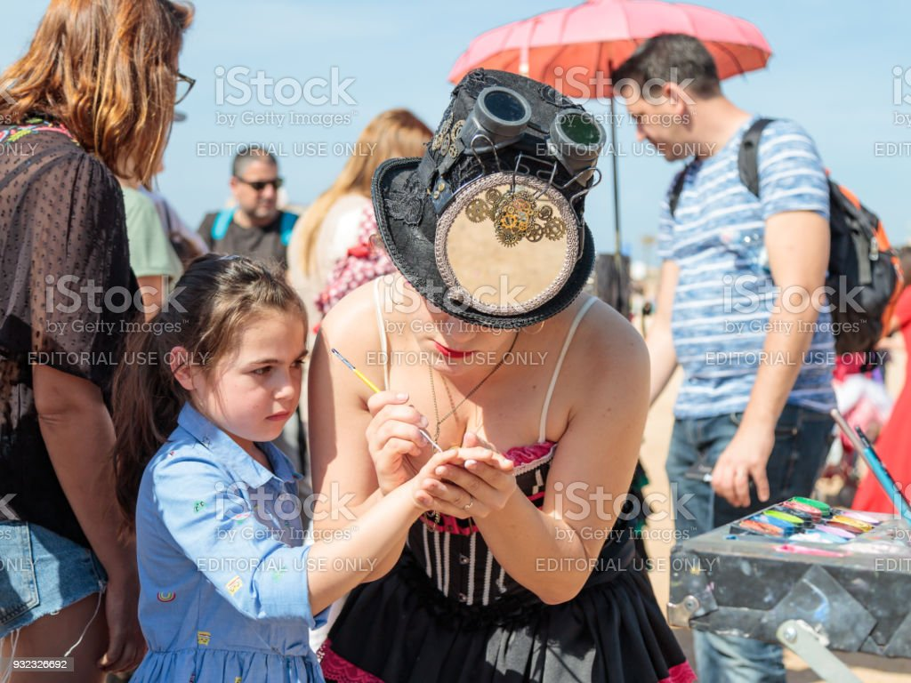 The participant of the Purim festival dressed in fabulous costume, puts a drawing on the girl's hand in Caesarea, Israel stock photo