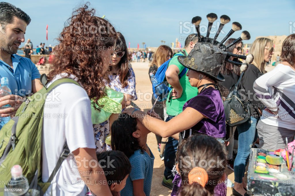The participant of the Purim festival dressed in fabulous costume, puts a drawing on the girl's face in Caesarea, Israel stock photo
