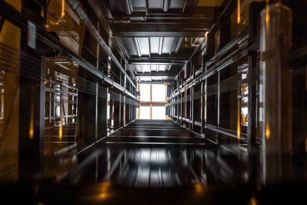 der beifahrerliftschacht, der von der glaskabine aus gesehen wird, ein verglastes dach an der spitze. - eingangshalle wohngebäude innenansicht stock-fotos und bilder