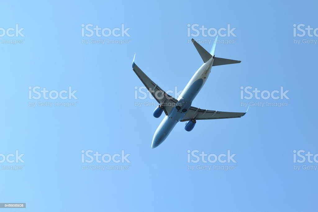 The passenger plane flies low overhead on a blue sky background. stock photo