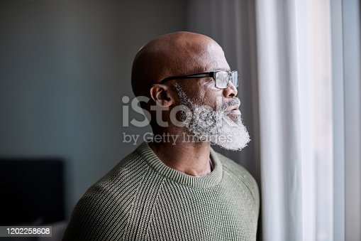 Shot of a mature man looking thoughtfully through a window at home