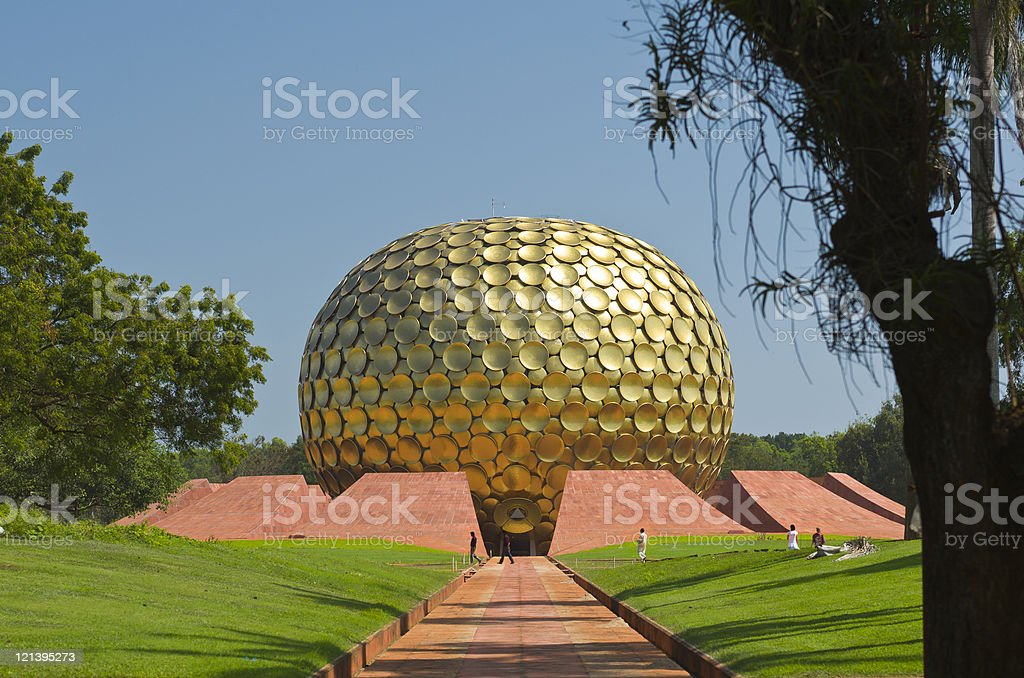 The path leading to entrance of Matrimandir in Auroville, India Photo of the path leading to the entrance of Matrimandir in Auroville, India. Green grass and trees surrounding the path. Blue sky behind the building. The Matrimandir is a location for meditation. Architecture Stock Photo