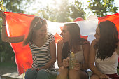 Three teenage girls pose witgh Canadian flag around them