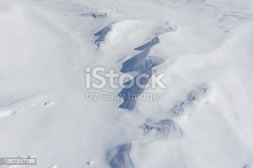 the pattern of snow drifts outlined by the wind as a natural background