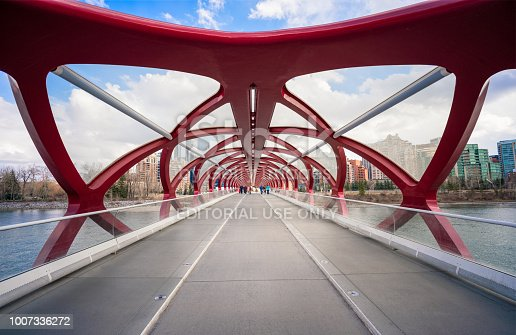 Calgary, Canada - A wide angle view of the unusual design of the Peace Bridge across the Bow River in Calgary, with pedestrians and cyclists crossing the bridge in the distance. The bridge was designed by Santiago Calatrava, and opened in 2012.