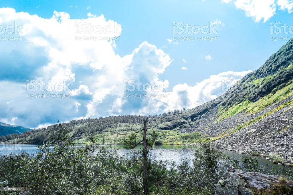 The peak view from the shore of a mountain lake. Journey through the hill country. Tourist attractions, natural beauty. stock photo