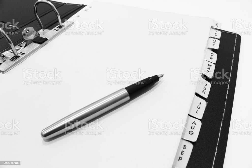 The Pen on Monthly Filing Sheets in the Ring Binder stock photo