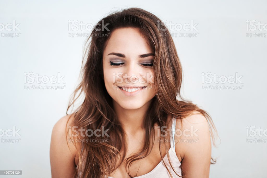 The pensive beautiful young girl smiles stock photo