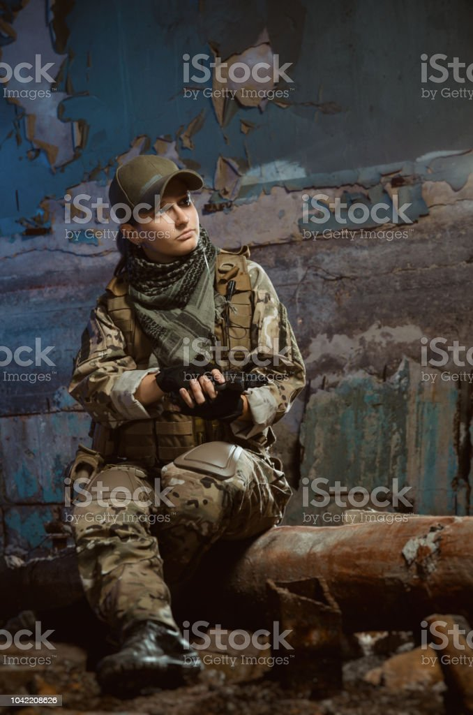 the people in uniform with weapons in the ruins stock photo