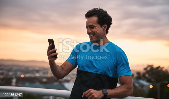 Shot of a young man using a smartphone during a workout in the city