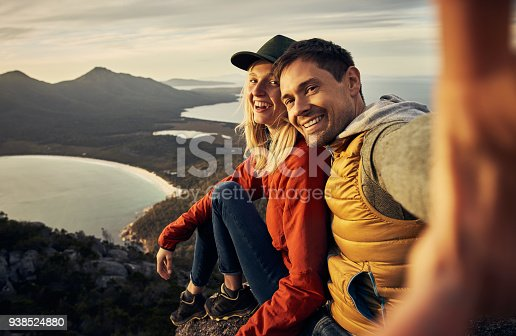 Cropped portrait of an affectionate young couple taking selfies while sitting on a mountain peak