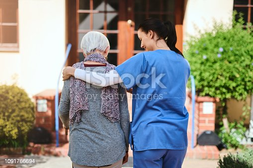 Rearview shot of a senior woman and a nurse going for a walk together in a retirement home garden