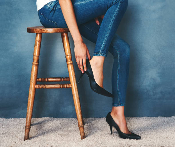The perfect fit Studio shot of an unidentifiable young woman trying on a pair of high heels against a blue background skinny jeans stock pictures, royalty-free photos & images