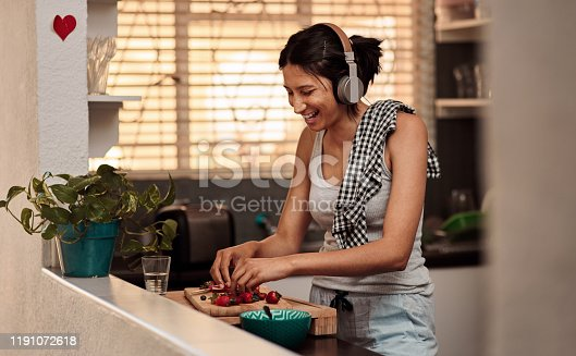 Shot of a young woman making a healthy snack with strawberries and listening to music at home