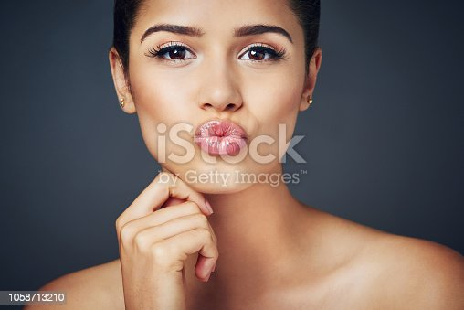 Studio shot of a beautiful young woman with flawless skin posing against a blue background