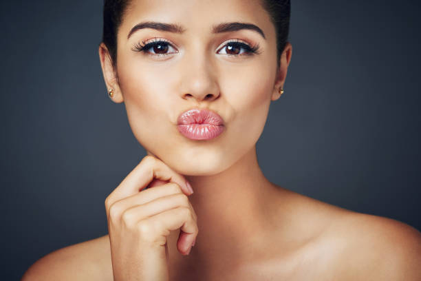 The perfect pout Studio shot of a beautiful young woman with flawless skin posing against a blue background puckering stock pictures, royalty-free photos & images