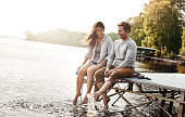Shot of a happy young couple sitting on a pier