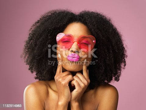 Studio shot of an attractive young woman wearing heart shaped sunglasses and pouting against a pink background