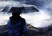 Shot of a woman covered with an umbrella watching a thunderstorm over a mountainhttp://195.154.178.81/DATA/i_collage/pi/shoots/783670.jpg