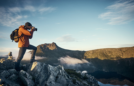 Shot of a young man taking photographs while hiking in the mountains