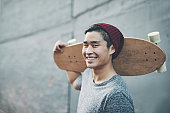 Shot of a young man holding a skateboard outside