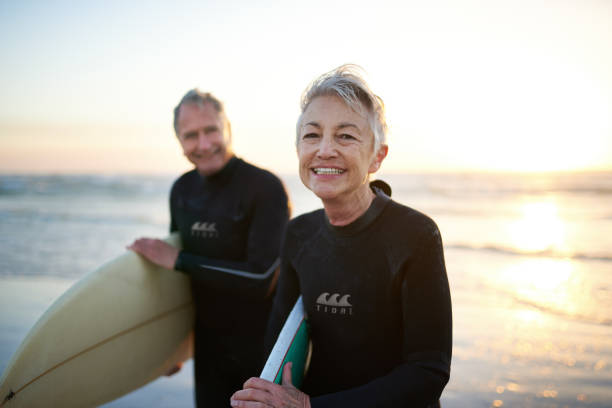 The perfect way to spend their free time Cropped shot of a senior married couple coming from surfing wetsuit stock pictures, royalty-free photos & images