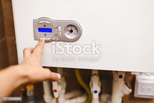 istock The person who regulates the heat in the central heating boiler. 1070666960