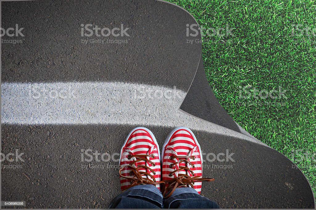 the person with sneakers standing on the asphalt, with green grass stock photo