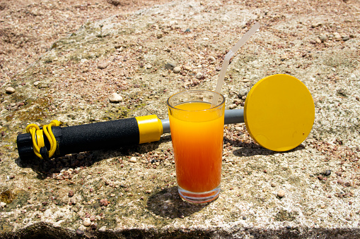 istock The photo of a glass of orange juice and underwater metal detector on the rock. Treasure searching and tourist adventure background. 1162205771
