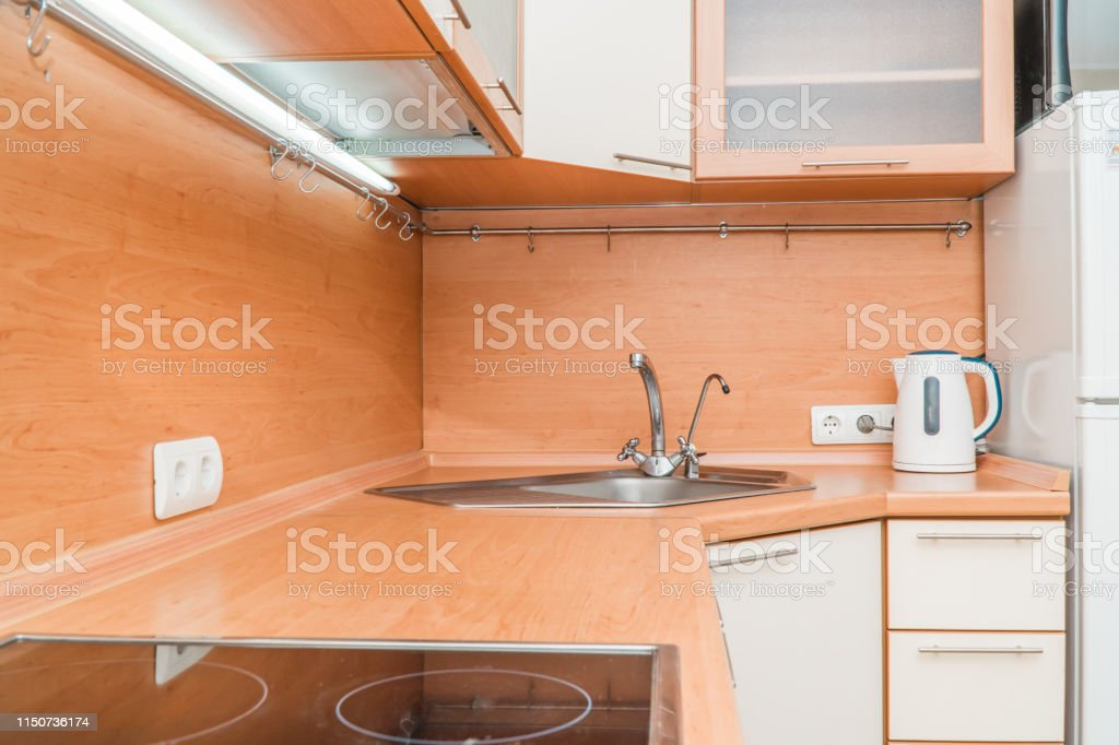 The photo of a white clean sink with the crane in the kitchen