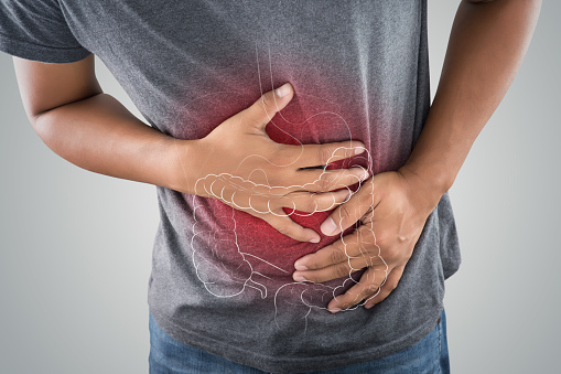 istock The photo of large intestine is on the man's body against gray background, People With Stomach ache problem concept, Male anatomy 962782170