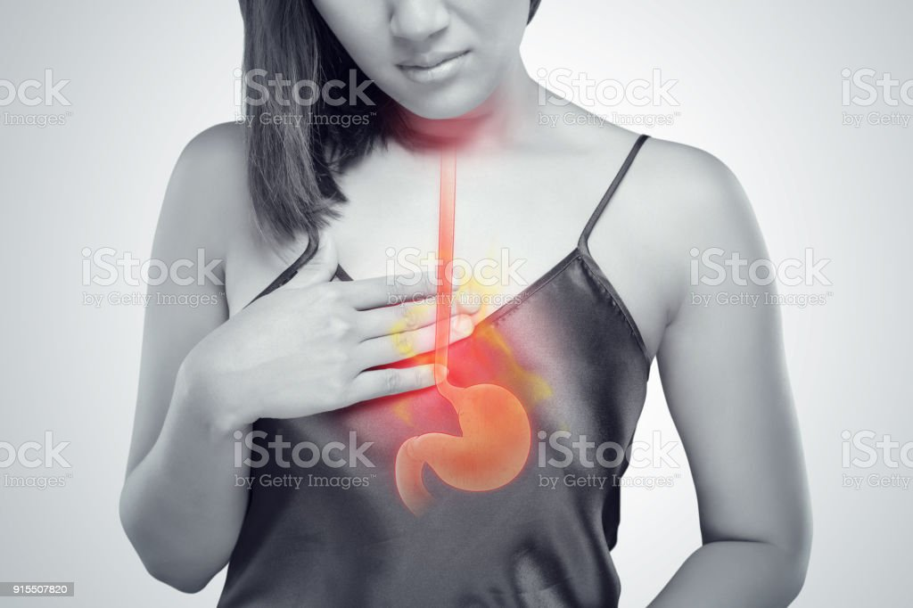 The photo of stomach is on the woman's body against gray Background, Acid reflux or Heartburn, Female anatomy concept stock photo