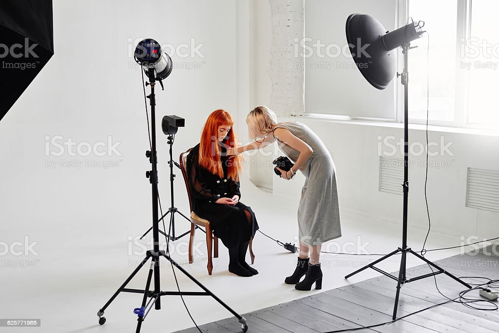 The photographer straightens hair fashion model on in Studio – Foto