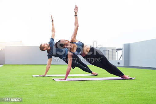 Shot of a young man and woman practising yoga together outdoors