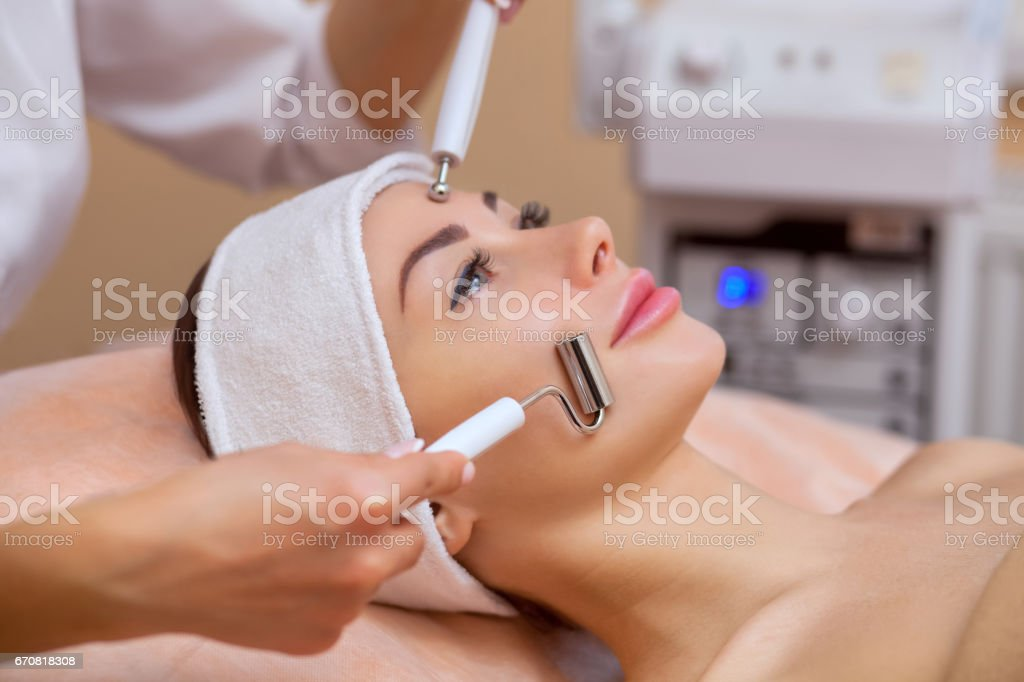 The physician-cosmetologist makes the apparatus a procedure of 'galvanic' ultrasound cleaning of the face skin of a beautiful, young woman stock photo